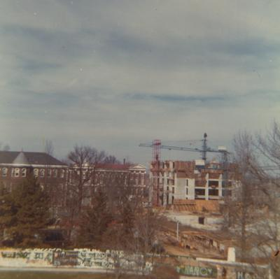 A color photo of the construction of Patterson Office Tower (right) near the Administration Building (center) and Miller Hall (left). This photo was taken from the window in room 518 in King Library on February 5, 1968 and donated by Terry Warth