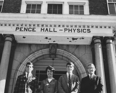 Three unidentified men and one unidentified woman are standing in front of Pence Hall (old Physics Building)