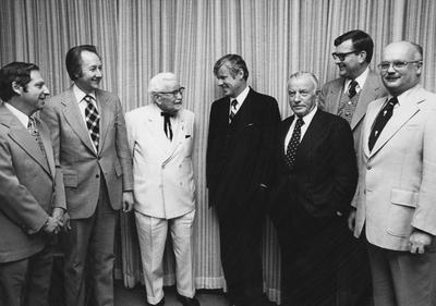 Seven men at the Sanders- Brown Center on Aging Building dedication. From left to right: Weck, unidentified man, Colonel Harland Sanders in white suit, Governor John Y. Brown, Jr., John Y. Brown, Sr., UK Vice President Ray Hornback, and Chancellor of Medical Center Peter Bosomworth. Received April 12, 1996 from the Medical Center Chancellor