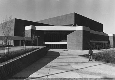 Photo of the front of the newly completed Singletary Center for the Arts. A young man walks toward the building carrying a book
