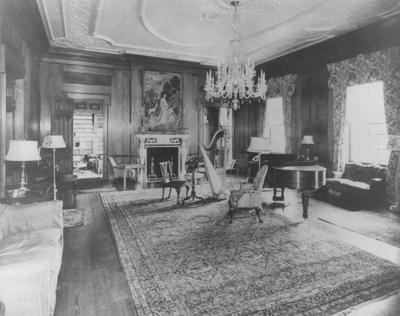 Music room adjacent to the library with a harp and piano in Spindletop Hall