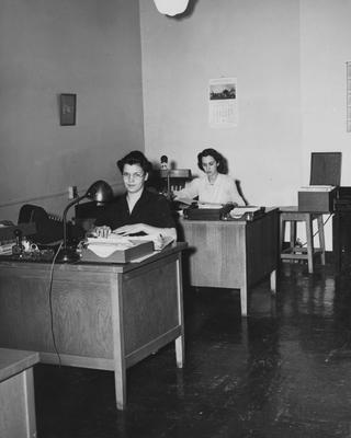 Helen Spickard (left) and Frances Brack (right) are seated at their desks in the Business Office. This photo appears first on page 16 in the 1941