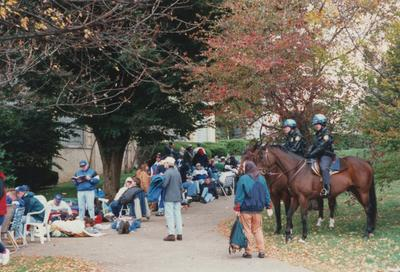 A color photo of unidentified people standing and sitting in line as well as two officers on horses at Memorial Coliseum for