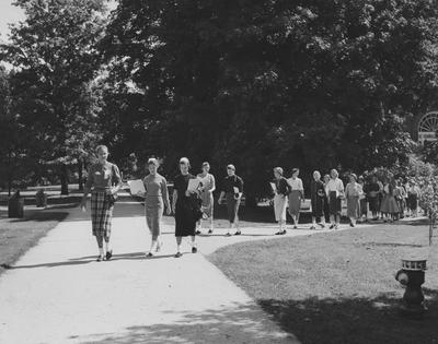 Registration and Freshman Week--group of freshman girls walking on campus; Susan Haselden is in the front, the next two girls are Margaret Fistrell and Susan Freed