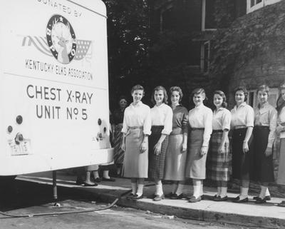 Registration--Group of female students beside an X-ray unit. From left to right: unidentified, Elaine Long, unidentified, Peggy Rollins, Joan Weggins, and Judy Semmons. Received September of 1957 from Public Relations