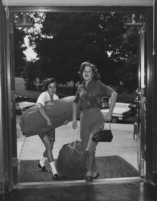 Two female students enter Frazee Hall with duffle bags to move in; woman on the right is Catherine Ward