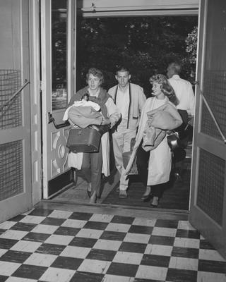 Students moving in; a man and two women. Received December 11, 1961 from Public Relations
