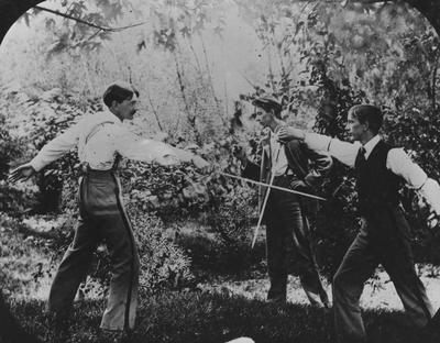 Two men fencing while another watches