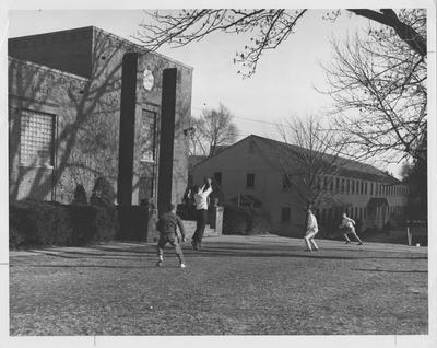 Left-Lafferty Hall; right-Social Science Building, demolished in 1949. Four men playing football in the yard. This photo appears first on page 215 in the 1963 Kentuckian