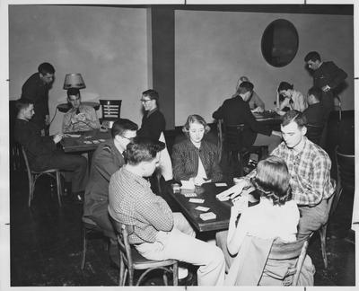 Students playing a Bridge game in the Student Union Building. Sitting at the back left table, on the far left, is John Wesley Faulkner