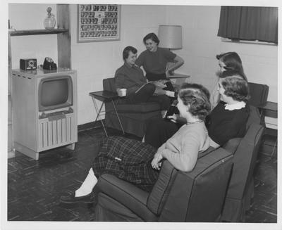 Three women watching television and two women reading a newspaper