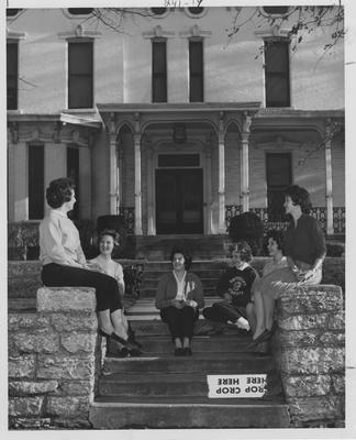 Six women talking outside the Hamilton House. From left to right: unidentified, Linda Lloyd, unidentified, Patricia Hager, unidentified, and Carole Ward. This photo appears first on page 241 in the 1963 Kentuckian