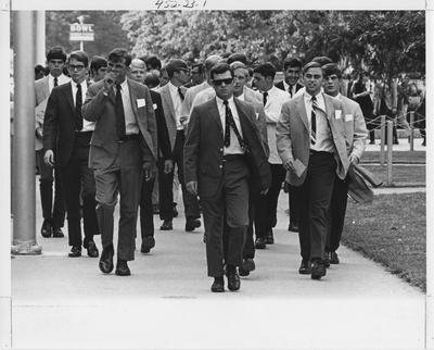 A large group of male students walking down a sidewalk on campus. This photo appears first on page 23 in the 1969 Kentuckian