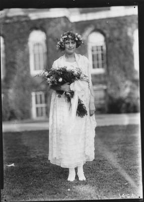 A young woman in a white dress, holding a bouquet of roses, wearing a flower headdress
