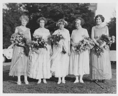 Five women in dresses with bouquets of flowers