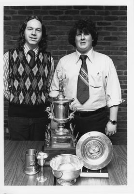 Two unidentified men standing with five trophies