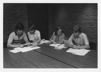 Mr. Mancuso (left) and Mr. Jones (right), an unidentified woman and an unidentified man are studying