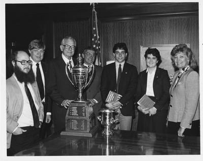 Debate Team left to right: Two unidentified men, UK President Otis Singletary, Harry Snyder, attorney and head of the Council on Higher Education, David Brownell, debate team member who won the national debate tournament, Ouita Papka, the first woman to win the national debate tournament and Governor of Kentucky Martha Layne Collins congratulating the UK student participants