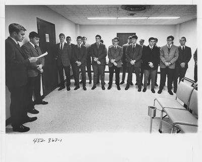 Keys: nineteen men standing in a room, one of the men is reading. This image appears first on page 363 in the 1969 Kentuckian