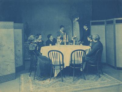Four unidentified women and four unidentified men sitting around a table