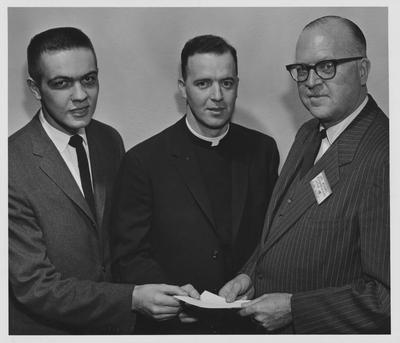 Religion in Life Week; An unidentified man (right), an unidentified priest (center) and Dr. Young are holding a piece of paper during the Religion in Life Week