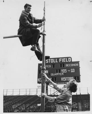 Steve Clark is sitting on a goal post at Stoll Field; Barbara Zweifel and Steve are wrapping streamers around a goal post, which earns points towards State University of Kentucky (SUKY) membership; State University of Kentucky (SUKY) is a pep organization that works with the University of Kentucky Athletic Association and its purpose is to promote school spirit. This photo is in the 1960 K - Book (student handbook) on page 8; State University of Kentucky (SUKY) was founded circa 1920