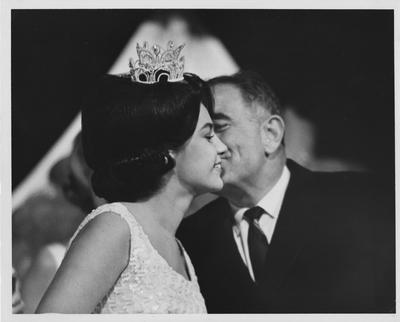 President Oswald kisses an unidentified queen in 1965; possibly Miss Kentucky or Miss Kentucky Derby on University of Kentucky campus; Kernel Photo; Photographer: Dick Ware