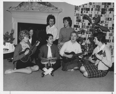 Girls playing instruments and singing at the Alpha Zeta Delta house; This image is in the 1962 Kentuckian on page 121, image 45
