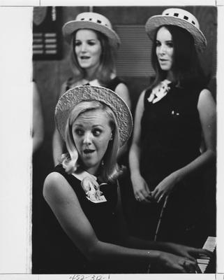 Delta Gamma sisters playing piano and singing; This image is in the 1969 Kentuckian on page 312, image 1