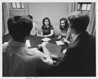 Alpha Epsilon Delta at a meeting; Facing camera are (left to right): Ron Weddle, Carolyn Purcell, and Becky Westerfield; Not facing camera are (left to right): unidentified, David Colvin; This image is in the 1969 Kentuckian on page 358, image 1