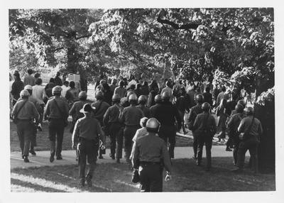 Armed guards follow the crowd of protesters during a reaction to the Kent State shootings