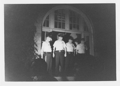 Police officers stand in the doorway of Barker Hall during a protest in reaction to the Kent State shootings