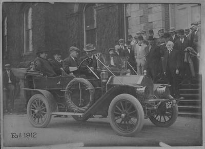 Red Oldsmobile parked in front of the University of Kentucky Administration Building; Driving: Dean F. Paul Anderson; Backseat: William Jennings Bryan and University of Kentucky President Henry B. Barker; University of Kentucky faculty members stand on steps in the background (bearded man on bottom left is University of Kentucky Vice - President and Professor of English James Garrard White)