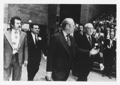 Former President Gerald Ford and United States Senator John Sherman Cooper spoke to a crowd of 7,000 in Memorial Coliseum in 1977; Vince Davis (in dark suit), Director of the Patterson School of Diplomacy in 1971 walks behind Ford and Cooper