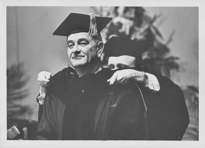United States President Lyndon B. Johnson, speaker at Centennial Convocation (1965, February 22), receiving an honorary degree; Placing an academic hood on the President is Kentucky Governor Edward T. Breathitt; Looking on at left, at podium, is University of Kentucky President John W. Oswald; Lexington Herald - Leader staff photo