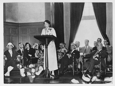 Eleanor Roosevelt addresses an audience in Memorial Hall; Seated behind her are Mrs. Morgenthau (spouse of Secretary of the Treasury, University President Frank L. McVey, and Governor Ruby Laffoon