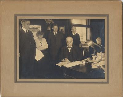 Governor A. O. Stanley signs a $200, 000 appropriations bill; Standing left to right: President Frank L. McVey; Miss Mahler; Richard C. Stoll, member Board of Trustees; Senator D. H. Peak; Treasurer John Shane