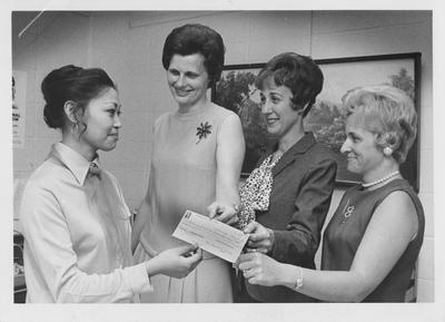 University of Kentucky Woman's Club makes a donation to the Nell Donovan International Student Loan Fund; Standing, left to right: Estella Fendley, University of Kentucky Assistant Foreign Student Advisor; Mrs. Robert Kiser, University of Kentucky Woman's Club; Mrs. Daniel S. Arnold, University of Kentucky Woman's Club Treasurer; Mrs. William Peters, University of Kentucky Woman's Club