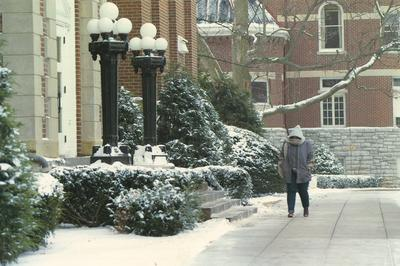 Student walks in front of the Administration Building on a snowy day; the Gillis Building can be seen in the background; 1997 calendar picture; Photographer: Nigel Scott