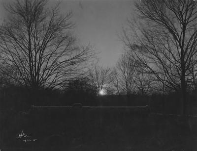 A cannon near the Administration building with sunrise or sunset in background; This is in the 1920 Kentuckian on page 12, image 1; Photographer: White Studio
