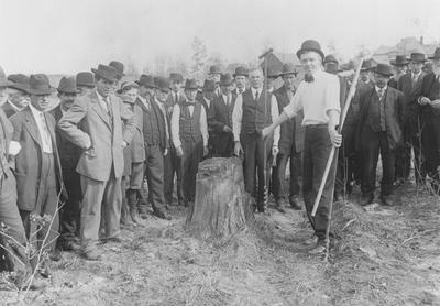 A man takes soil cores as a group watches