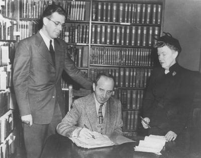 Author - critic Ben Lucian Burman autographs the original manuscript of his novel,
