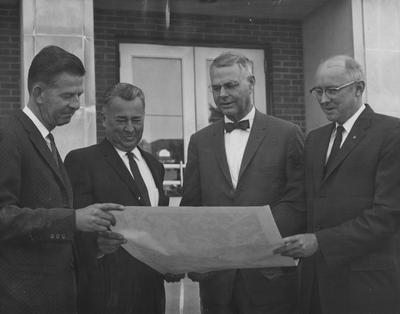 Looking over a section map similar to what they will produce en masse for the entire state are, from left to right: A. D. Zapp, United States geologist in charge; E. R. Branson, aerial geologist for Kentucky Geological Survey; Dr. C. A. Anderson, chief geologist of the U. S. Geological Survey; and Dr. Wallace Hagen, director and state geologist of the Kentucky Geological Survey