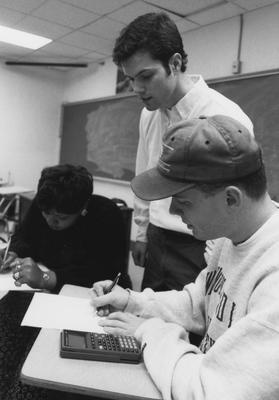 Communi - K MathExcel teaching assistant Pat Ward, standing, helps students Kim Carter (left) and Brandon Kessinger