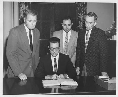 Discussing a clinical psychology internship are Dr. Frank M. Gaines (seated), commissioner in the Department of Health, and standing from the left, Dr. James S. Calvin, head of the University of Kentucky Department of Psychology; Dr. Kenneth Purcell, director of the clinical psychological training program in Kentucky; and Dr. Logan Gragg, superintendent at Eastern State Hospital, Lexington