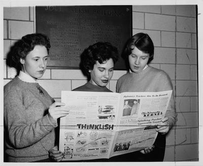 University of Kentucky Pre - Journalism scholarship recipients checking over a current edition of the University of Kentucky student newspaper,