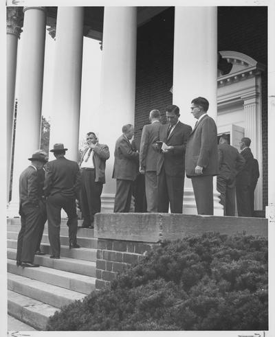 Men attending an Educational Conference smoke and talk outside Memorial Hall