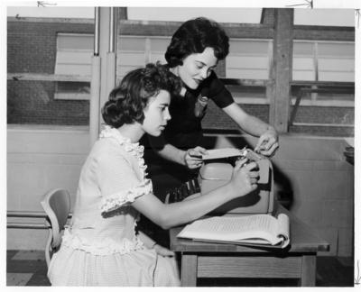 Student teacher Debbie Daniels is helping a female student with a typewriter