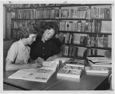 Two women students find materials for supplementing classroom textbooks in elementary and secondary education in the College of Education Library; This image is in the 1963 Kentuckian on page 272, image 1