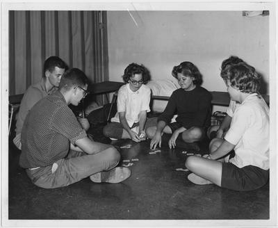 People playing cards in a fallout shelter at the University of Kentucky Taylor Education Building; The stay was part of the training in University of Kentucky's shelter manager instructor class; The group went through Civil Defense procedures just as they would in an actual emergency; Lexington Herald - Leader